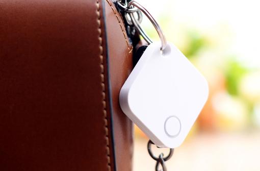 Porte clé connecté blanc accroché à un sac