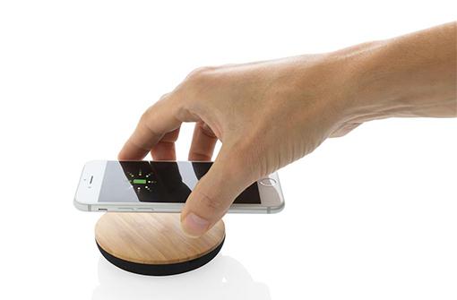 Chargeur à induction rond en bambou naturel avec une main qui pose un smartpone dessus