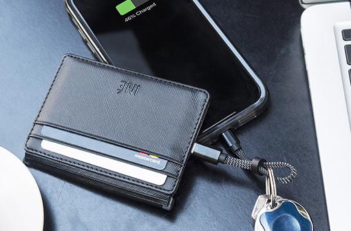 Porte cartes anti RFID avec powerbank branché sur un smartphone posé sur le dessus d'un bureau